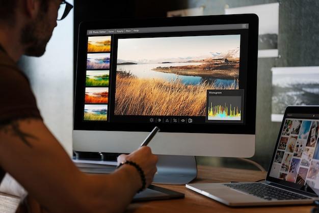 Hombre editando fotos en una computadora Foto gratis