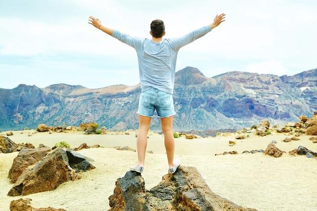 Hombre elegante feliz en ropa casual hipster de pie en el acantilado de la montaña con las manos levantadas al sol y celebrando el éxito Foto gratis