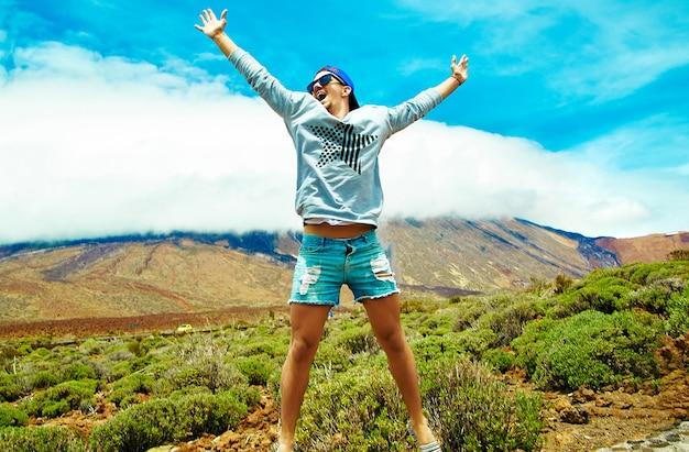 Hombre elegante feliz en ropa casual hipster saltando frente a la montaña con las manos levantadas al sol y celebrando el éxito Foto gratis