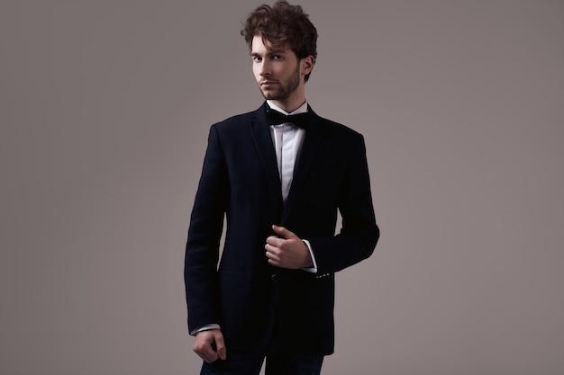 Hombre elegante guapo con el pelo rizado con esmoquin Foto Premium