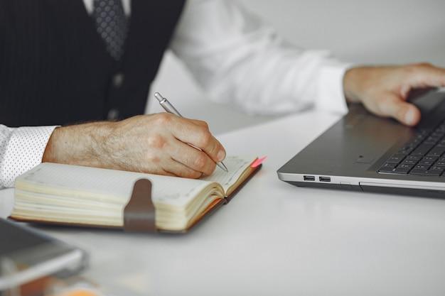 Hombre elegante en la oficina. hombre de negocios con camisa blanca. el hombre trabaja con un portátil. Foto gratis