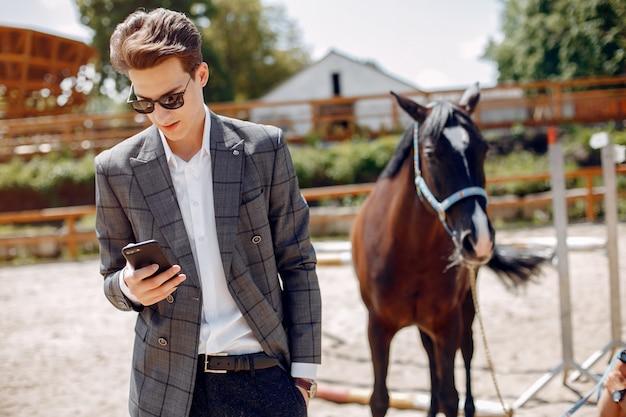 Hombre elegante de pie junto al caballo en un rancho Foto gratis
