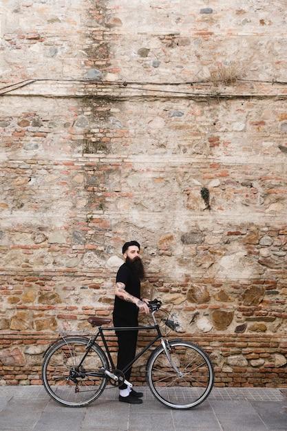 Hombre elegante de pie con su ciclo frente a la pared de ladrillo viejo Foto gratis