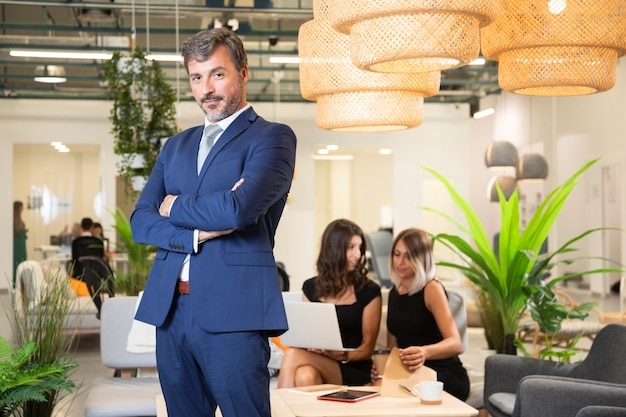 Hombre elegante posando en traje en la oficina Foto gratis