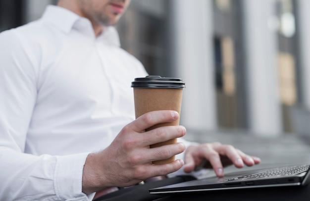 Hombre elegante que sostiene la taza de café Foto gratis