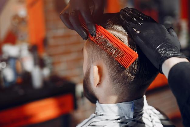 Hombre elegante sentado en una barbería Foto gratis