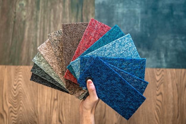 El hombre elige el color de la alfombra nueva de acuerdo con el libro de patrones en la tienda de pisos Foto Premium