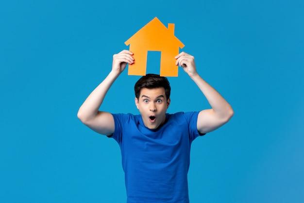 Hombre emocionado sosteniendo un modelo de vivienda en lo alto Foto Premium