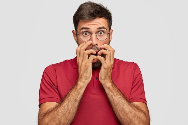 Hombre emocional joven preocupado posando contra la pared blanca Foto gratis