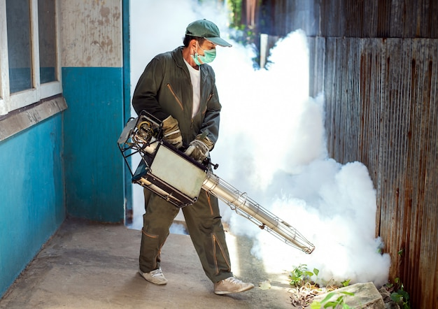 El hombre se empaña para eliminar el mosquito y prevenir la propagación del dengue y el virus del zika Foto Premium