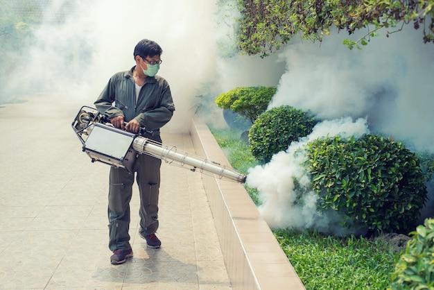 El hombre se empaña para eliminar el mosquito para prevenir la propagación de la fiebre del dengue y el virus zika Foto Premium