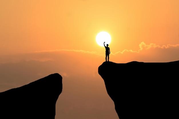 Hombre en la parte superior de la montaña, el hombre de la libertad en el fondo puesta del sol Foto Gratis