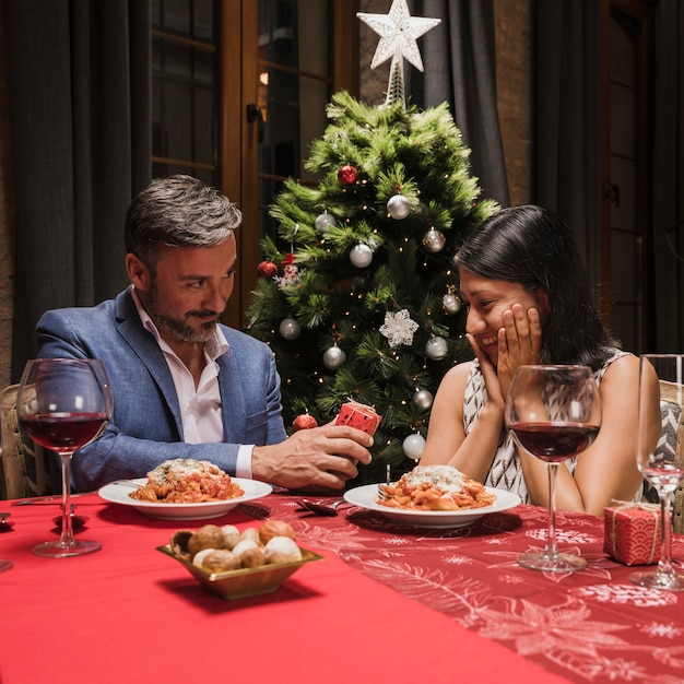 Hombre encantador y mujer cenando en navidad Foto gratis