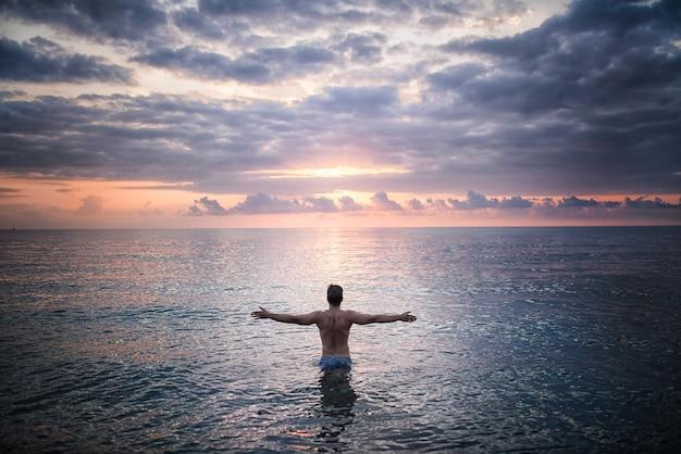 El hombre se encuentra en el agua de mar frente a la puesta de sol Foto gratis