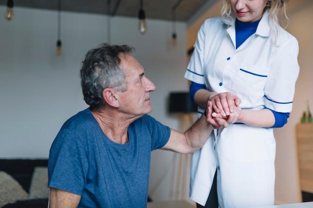 Hombre y enfermera simpática en asilo de ancianos Foto gratis