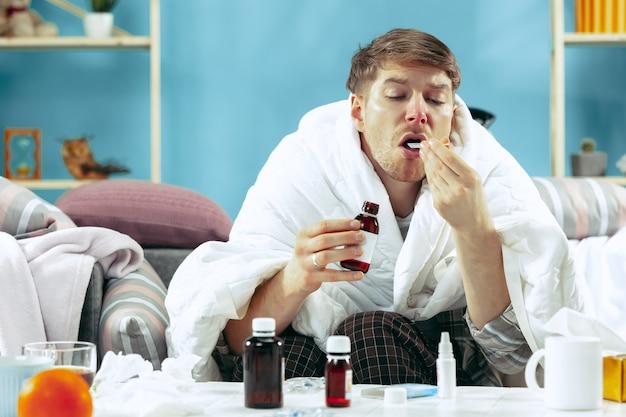 Hombre enfermo barbudo con chimenea sentado en el sofá en casa cubierto con una manta caliente y bebiendo jarabe de tos. la enfermedad, la gripe, el concepto de dolor. relajación en casa Foto gratis