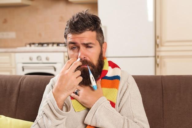 Hombre enfermo con un termómetro en la boca. joven comprobando sus síntomas. autoaislamiento. hombre barbudo que se queda en casa. c Foto Premium