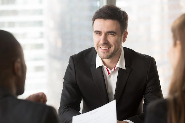 Hombre enfocado en conversar con entrevistadores. Foto gratis