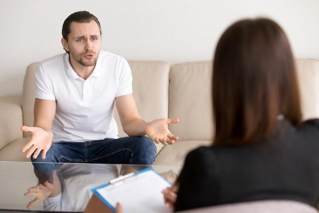 Hombre enojado con problemas que se queja a la psicoterapeuta femenina, hablando de problemas Foto gratis