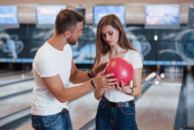 Hombre enseñando a niña a sostener la pelota y jugar a los bolos en el club Foto gratis