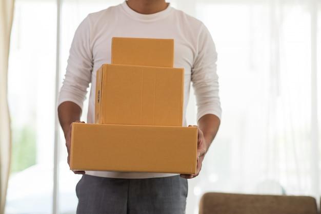 Hombre de entrega logístico sonriente joven que sostiene la caja Foto gratis