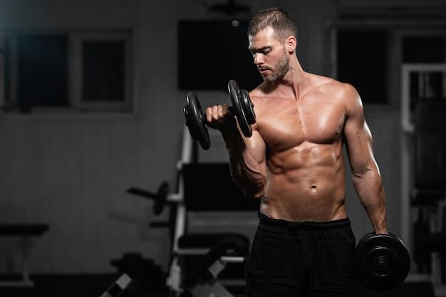 Hombre entrena en el gimnasio. hombre atlético entrena con mancuernas, bombeando sus bíceps. Foto Premium