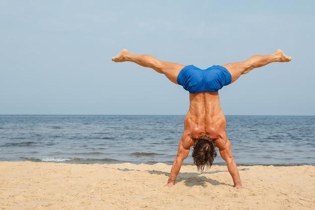 Hombre durante el entrenamiento en la playa Foto Premium