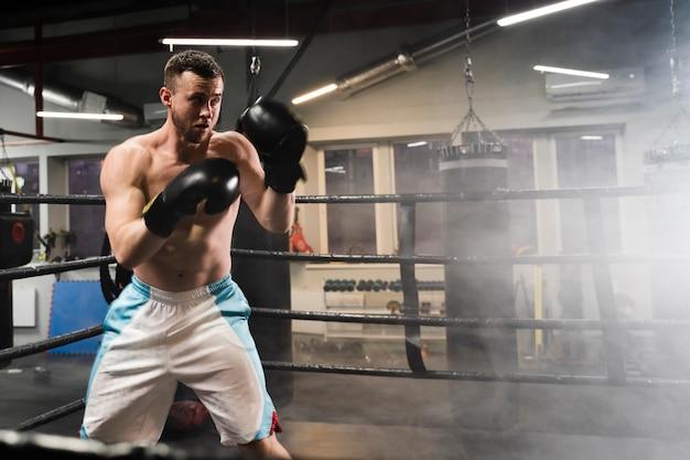 Hombre entrenando en ring de boxeo Foto gratis