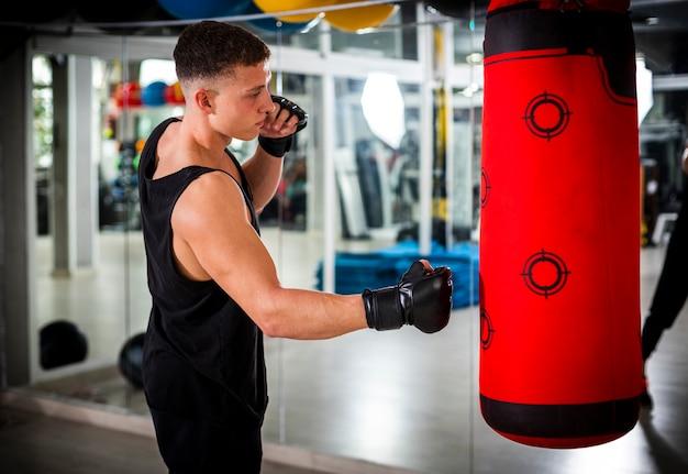 Hombre entrenando con saco de boxeo Foto gratis