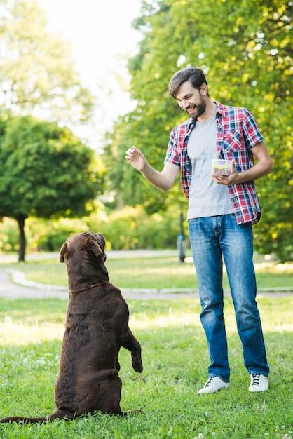 Hombre entrenando a su perro en el parque Foto gratis