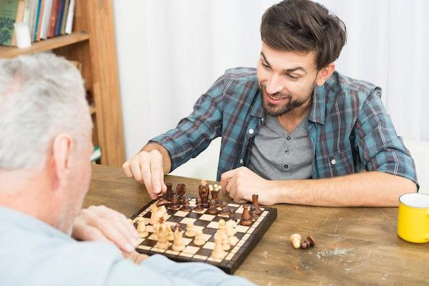 Hombre envejecido y chico feliz joven jugando al ajedrez en la mesa en la habitación Foto gratis