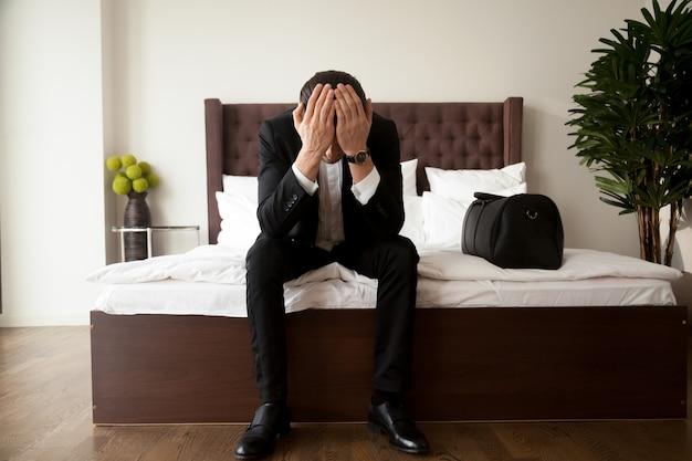 Hombre con equipaje llora en el hotel después del divorcio Foto gratis