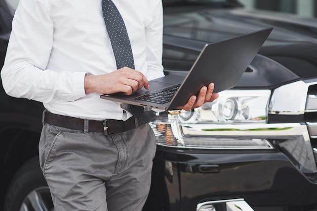 El hombre es un hombre que trabaja en una computadora portátil y prueba en dispositivos móviles. Foto gratis