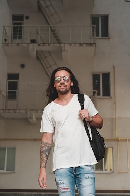 Hombre en escena urbana con mochila y gafas de sol Foto gratis