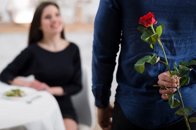 Hombre escondiendo una rosa roja de su novia Foto gratis