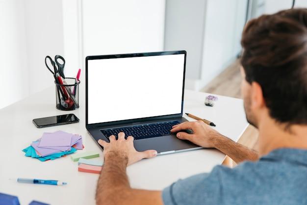 Hombre escribiendo en la computadora portátil en el escritorio con papelería Foto gratis