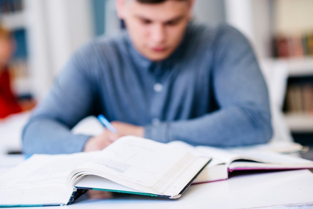 Hombre escribiendo sobre la mesa con libros Foto gratis