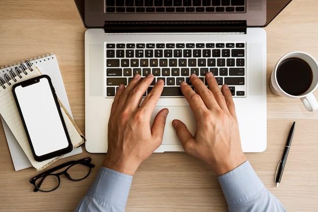 Hombre escribiendo en la vista superior del portátil Foto gratis