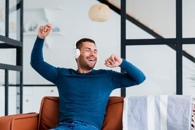 Hombre escuchando música y bailando en homr Foto gratis