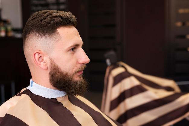 Hombre esperando que se arregle su barba Foto gratis