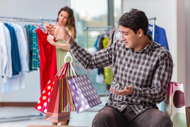 Hombre esperando a su esposa durante las compras navideñas Foto Premium