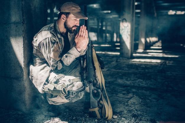 El hombre espiritual está sentado en posición en cuclillas y rezando. mantiene los ojos cerrados y las manos juntas cerca de la cara. también hay un rifle cerca de sus rodillas. Foto Premium