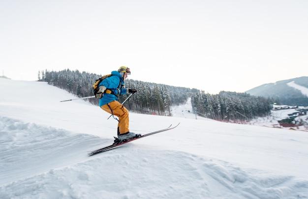 Hombre esquiador al saltar desde la ladera de las montañas Foto Premium
