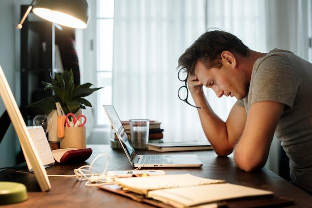 Hombre estresado mientras trabajaba en la computadora portátil Foto Premium