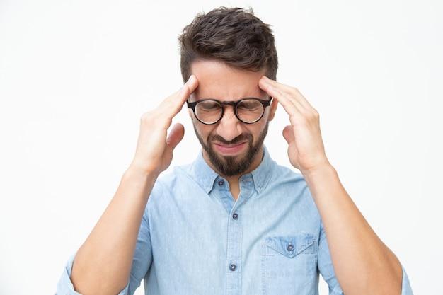 Hombre estresado que sufre de dolor de cabeza Foto gratis