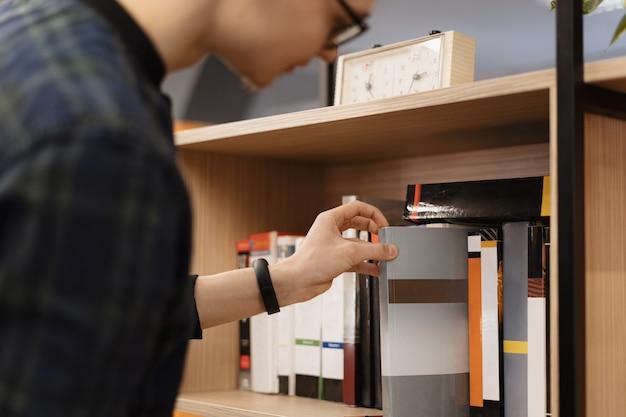Un hombre estudiante recogiendo libros del estante Foto gratis