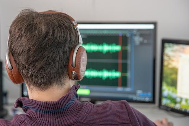 El hombre en el estudio fotográfico graba y modifica el canto, la voz y la música para uso comercial. funciona en un editor de audio en una computadora con auriculares Foto Premium