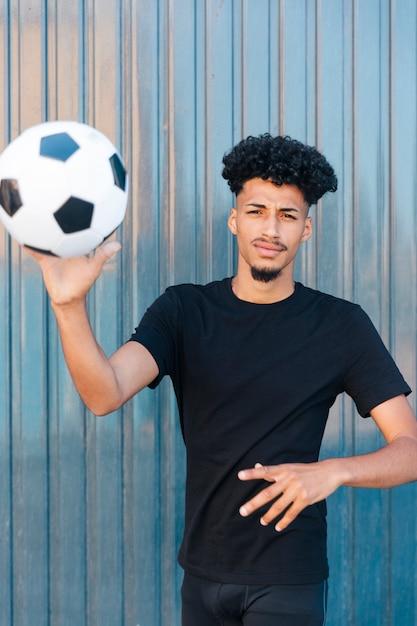 Hombre étnico lanzando fútbol a la cámara Foto gratis