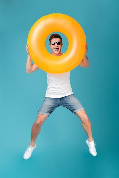 Hombre excitado feliz en gafas de sol con anillo inflable y saltando Foto gratis
