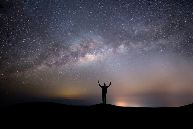Hombre exitoso silueta en la cima de la colina sobre un fondo con estrellas Foto gratis